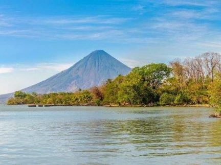 Photo of a lake in Nicaragua with trees along the shoreline and the Conception volcano in the background against blue skies with light cloud.