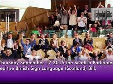 Crowd of people with their arms in the air celebrating the passing of the British Sign Language (Scotland) Bill on September 17th 2015.