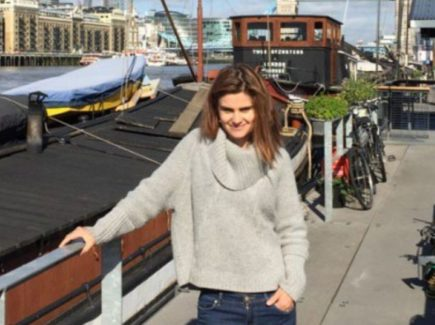 Jo-Cox-wearing-a-grey-jumper-and-jeans-standing-by-the-River-Thames-and-smiling-at-the-camera.