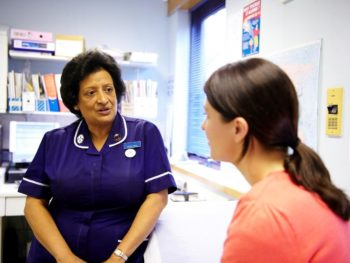 Photo of a female cancer patient sitting in a doctor's surgery and speaking with a Cancer Research UK nurse.