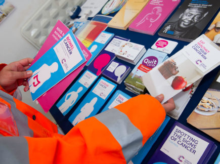 Person browsing a selection of informative leaflets about cancer and early diagnosis created by Cancer Research UK.
