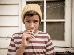 Photo of a child smoking created for a Cancer Research UK campaign to protect children through standardised tobacco packaging.