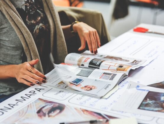 Picture of a lady reading news or preparing PR and press release plans with magazines spread out in front of her
