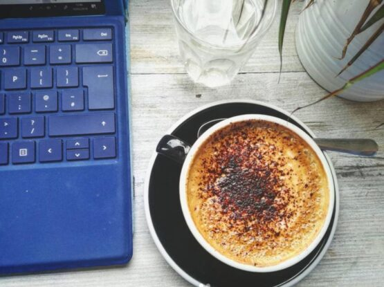 Birds eye view of a cappucino, glass of water and a laptop to illustrate Melissa's daily freelance life