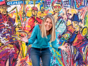 Sally Dear from Ducky Zebra smiling and standing in front of a colourful wall with brightly coloured images of people painted on it