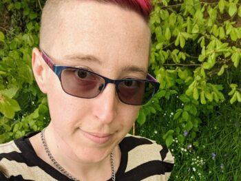 Alexis with pink hair, sunglasses and a striped top smiling at the camera
